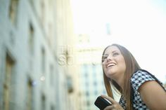 Young woman in city with mobile phone