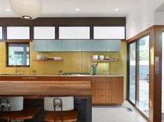handmade + modern together. rectangles & lines: windows, tile, cabinets, cabinet veneers, island countertop, counter chairs. Sunny Mid-Century Modern Kitchen | FireClay Tile color: Daffodil
