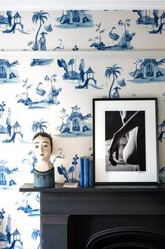 Fireplace surrounded by blue and white wallpaper