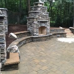 Fireplace and belgards bel-air wall as seating with natural stone boulders