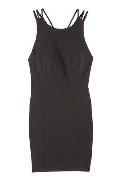 Robe courte en jersey: Robe courte et ajustée en jersey crêpé. Modèle avec découpe haute devant et bretelles triples croisées dans le dos. Fermeture par zip dissimulé dans le dos. Doublée jersey.