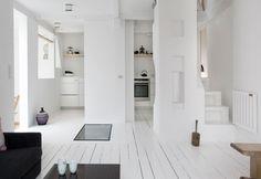 Atmosfera serena e look in total white per il living a pianta aperta di Vedbaek House, abitazione di inizio Novecento ristrutturata da Norm Architects in un villaggio danese