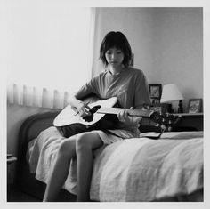 This photo brings my eyes to the light of the curtain and the contrasting black hair of the woman. Then it brings my eyes to where she's looking at, the guitar.