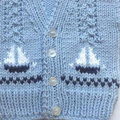 Edad 0 - 6 meses. Este cardigan de niño bebé tiene pequeños veleros azules marino en el frente y se teje en un peso mediano, hilado de acrílico, en un dulce color azul claro. La chaqueta tiene un V cuello y mangas largas. Un regalo ideal para un nuevo bebé. Las mediciones están por