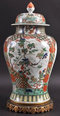 """A 19TH CENTURY FAMILLE VERTE BALUSTER VASE AND COVER. Painted with buddhistic lions and panels of birds in flight. Vase is 13.25"""" high"""