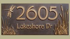 This cattail and dragonfly address plaque is custom carved and cold coated with copper or brass.