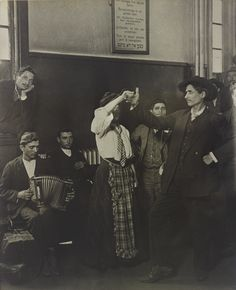 """Immigrants Dancing At Ellis Island"", c.1905.  ~ American sociologist and photographer: Lewis Wickes Hine, (1874-1940). ~ Interesting to note, that the sign on the wall, ""No Charge For Meals Here"", is displayed in different languages, so the immigrants from various countries could read it. ~ {cwlyons} ~ (Image/Auction - Sotheby's)"