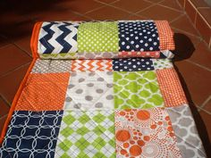This nautical themed patchwork quilt in navy blue, grey, orange and lime green measuring 32 by 40 would be perfect for the nursery as a crib quilt