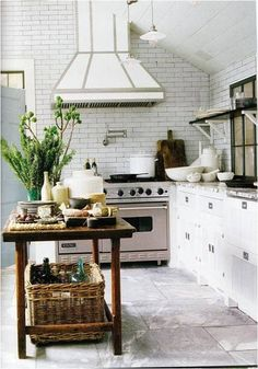 The center of attention in this kitchen is the center island - filled with all the goods, wooden baskets, and fresh greenery, it's eye catching and cute.