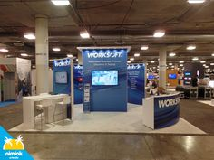 Worksoft 20x20 Custom Trade Show Booth Exhibit. Created for the SAP HR TECH 2016 in Las Vegas. The design included four custom curved demo stations with LED puck lighting and vinyl applied graphics. A branded closet/tower and reception counter with hidden storage where added for design and efficiency.