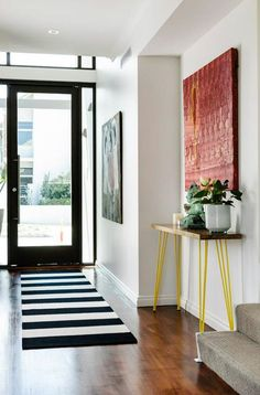 Entrance with striped rug and yellow hairpin table.