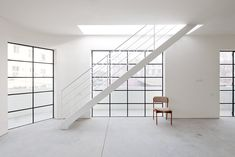 Minimalist stairway and concrete floor. Renovated apartment building by A N +. Photo by Aviad Bar Ness.