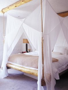 The platform bed and mosquito-net drapery deliver a whimsical and romantic feel to this master bedroom. Textural rope, rustic wood logs and white linens bring the outdoors in and deliver simple serenity.