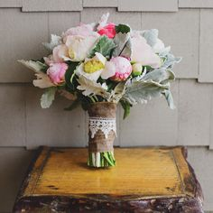A mixed-bloom bouquet wrapped in burlap and homespun lace.