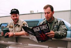 Law enforcement officer Paul Budrow, right, reads a copy of High Times magazine, as officer Wray Graham looks on, while waiting to be deployed to a marijuana patch near Ukiah, Calif., Tuesday Sept. 22, 1998. They read the magazine to keep up on the drug culture. Officers come from across the state to spend eight weeks with the multi-agency task force called CAMP - the Campaign Against Marijuana Planting.  In camouflage, they swoop onto hillsides from helicopters and use machetes to hack…