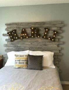 DIY recycled wood fence panel headboard, whitewashed with light up marquee letters from Michael's. It took one morning to assemble, whitewash, and hang on wall.