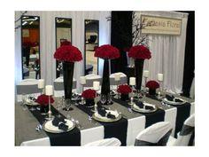 Decoración de boda en negro con arreglos de flores en rojo