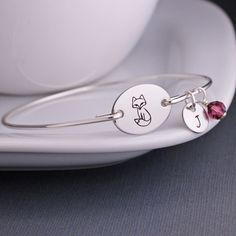 The bangle is hand formed from stainless steel wire and then hand-hammered and tumbled for shine and strength. The stainless steel circle is engraved with a little fox and measures 3/4 inch across. **
