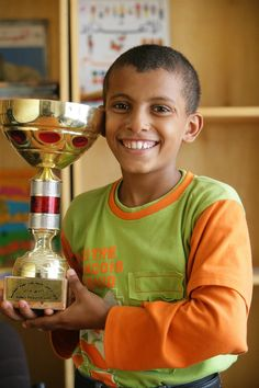 Abdullah, 11, smiles as he displays the trophy he won at the 'Safe Children Centre', a UNICEF-supported residence for vulnerable children in Aden, Yeman. Most of the boys who live at the centre formerly lived on the streets, having migrated to the city from the countryside to seek work or escape violence at home. UNICEF finances the centre which houses 40 boys, and has provided all supplies, including learning materials, furniture, toys and games. © UNICEF/Giacomo Pirozzi http://www.unicef.org