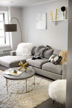 a comfy grey, creamy and gold living room with a large grey sectional sofa that takes half a space
