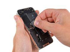 * Använd den genomskinliga plastfliken för att försiktigt lyfta ut batteriet ur iPhone.  * Var försiktig när du drar ut batteriet med plastfliken. På vissa enheter använder Apple en överdriven mängd lim, vilket gör det praktiskt taget omöjligt att ta bort batteriet på detta sätt.