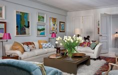 Soft grey Upper West Side living room with pops of bright colors, exotic textiles and lots of abstract art