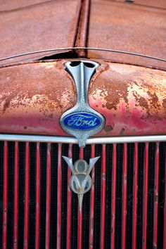 V8 symbol on the front of an old 1930's Ford flatbed pickup truck grille, rustic Americana weathered, worn, and faded red.