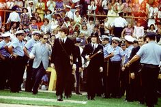 Bob Bonis escorts the Beatles onto the field to take the stage at Comiskey Park, in Chicago, August 20, 1965.