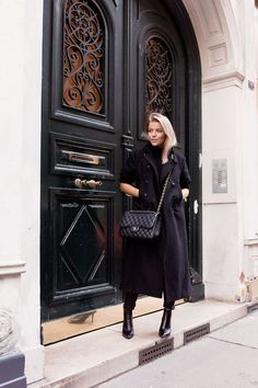 Elegant black on black outfit. Black trenchcoat, black chinos, black classic Chanel bag and black simple heels.
