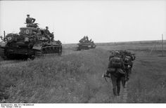 An infantry section is passed by a zug (platoon - 3-5 tanks) of Panzerkampfwagen IV medium tanks, East, 1943