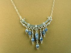 """This Bohemian inspired curved bar pendant necklace is hand crafted from Sterling silver wire and adorned with denim blue sodalite and sterling silver bead fringe. The 2"""" long and 2"""" wide pendant is attached to 16"""" of a delicate Sterling silver flat cable chain and has a Sterling silver lobster claw clasp."""