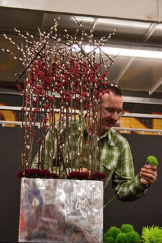 David also made another tall design using a base structure of pussy willow and ilex, as you can see below. Deep red carnations and Green Trick sweet williams were added to the arrangement, together with Anastasia green chrysanthemums. Christmas Flower Arrangements, Floral Arrangements, Modern Floral Design, Floral Designs, Chinese New Year Flower, Hotel Flowers, Red Carnation, Flower Decorations, Table Decorations