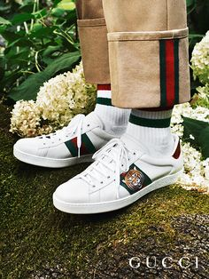 Presenting gifts from the Gucci Garden. The House Web stripes appear on trousers, socks and the Gucci Ace sneakers—decorated with an embroidered tiger head—in the Gucci Gift by Alessandro Michele.