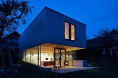In diesem freistehenden Wohnhaus in Freising fühlt man sich dank großer Glasflächen und viel warmem Holz der Natur verbunden.