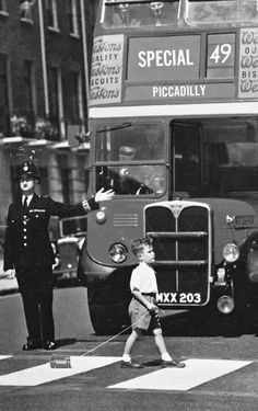 A boy crosses in front of a double-decker bus, pulling a miniature version behind him.  1950s, UK.