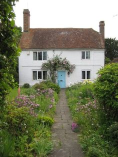 Adorable French country cottage with a garden pathway and painted blue front door.