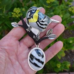 "Oh little yellow-throated warbler, I'm quite enamored with you! I tried to post this as a video a short while ago, so that I could show you the back. But the result on IG was a low resolution mess - is this another wonderful IG ""improvement""? OK back to the bird - this is cloisonné on fine silver in a sterling silver setting, paired with a Utah zebra stone custom cut for this piece.   #warbler #yellowthroatedwarbler #cloisonné"