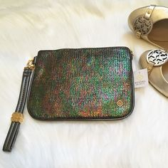 """HP NWT Kendra Scott Iridescent Medium Wristlet HOST PICK- NWT Kendra Scott Medium Wristlet! Color: Dark Iridescent. The colors this shows in varying light is GORGEOUS! DETAILS: Simply throw in everything you need for a night on the town. Custom-designed detachable handle adds versatility while the sleek iridescent woven exterior gives a playful pop to any outfit. DETAILS •14K Gold plated metal hardware • Size: 8.25""""L x 6.5""""W w 7""""detachable wrist strap • Interior zip pocket •Material: woven…"""