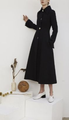 Shop now. REJINA PYO Black Linda Long Panelled Coat.  The Vogue Edit. Black double-faced twill coat with shaped panels. Slim-fitting at the waist with front button fastening and voluminous hem. Fully lined.