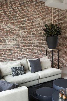 """De karakteristieke wand met steenstrips met baksteen look en houten meubels met stalen poten geven het interieur een industriële look. Foto: Denise Keus – """"Stijlvol Wonen"""" - © Sanoma Regional Belgium N.V."""