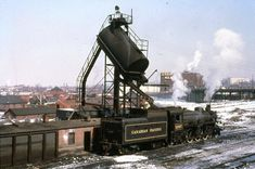 A hopper loading coal into steam locomotive's coal car in a train yard station. Old Steam Train, Canadian Pacific Railway, Railroad Pictures, Railroad History, Train Truck, Old Trains, Train Pictures, Model Train Layouts, Steam Locomotive