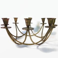 Mid century brass, centerpiece candelabra. This candelabra is a beautiful, graceful piece for table decor with 8 candle holders in a base forming an elegant circular geometric shape.  It has been left with its original patina and has not been polished.