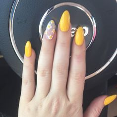 Yellow almond gel nails with flower accent