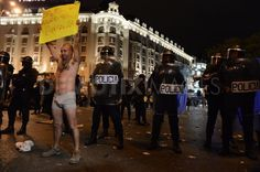 A semi-naked demonstrator stages a non-violent protest in Neptuno's Square, near the Spanish Parliament during renewed protests over austerity measures.