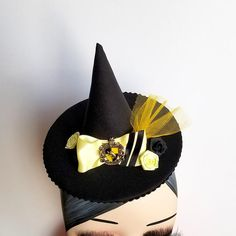 Show your house spirit with this miniature witch's hat! Small and sassy, it features satin ribbon, roses and a house crest on black crepe. Attaches with two a