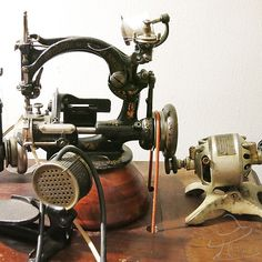 Straw Braid Sewing Machine; operate by treadle or friction motor.  The motor to the far right is a Hamilton Beach Home Motor friction motor that is a few years from being 100 years old.  It has a spring that pushes up against the wheel and turns it. The motor can be set to move the wheel forwards or backwards.  The belt is shown in place for image purposes only, as it is not needed when the friction motor is engaged.