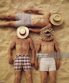 Aerial view of three men lying shirtless on the beach, with hats covering their faces, California, ca.1965.