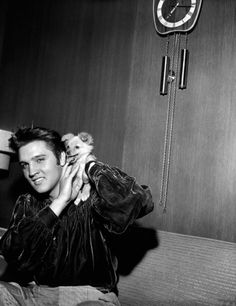 Elvis Presley plays with his puppy Sweet Pea on, 1956.