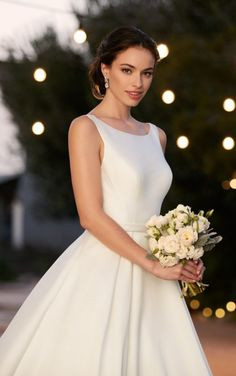 This modern A-line wedding gown from Martina Liana boasts a sophisticated neckline, slimming waist belt, hidden pockets, and a lightly pleated skirt that flows into a cathedral train. The mid-cut back features eye catching straps and zips up under fabric covered buttons.  http://www.charlottesweddings.com/for-the-bride/request-appointmen/