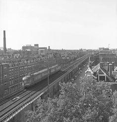 Het spoorviaduct van de Hofpleinlijn met een passagierstrein boven de Vijverhofstraat, waarschijnlijk 1965.
